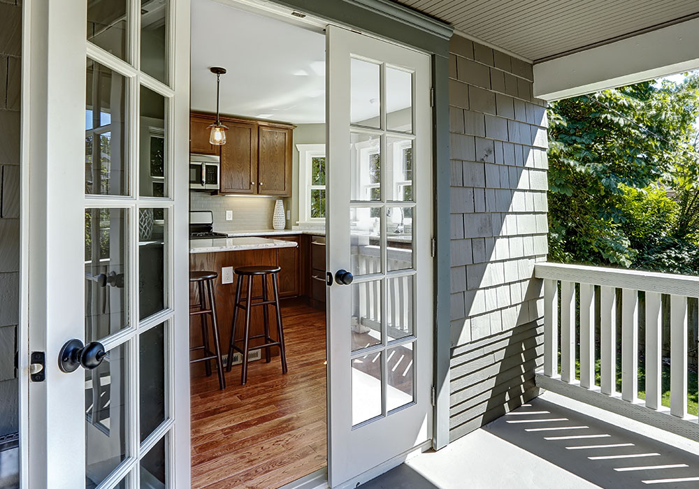 Custom exterior french doors opening up to the back yard with a brief view of the beautiful kitchen.