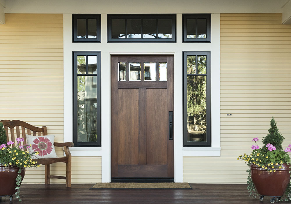 A custom built wood door with a custom windows on top and each side of the wood door.